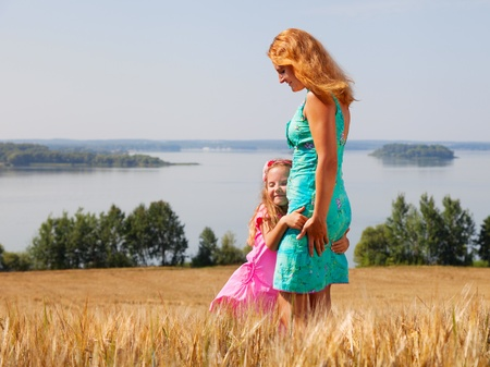 little girl hugging her mother in a wheat field near lake on a sunny day photo