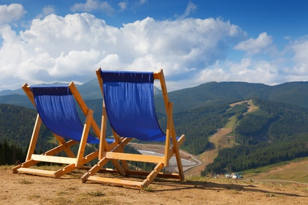 two blue deckchairs in mountain photo