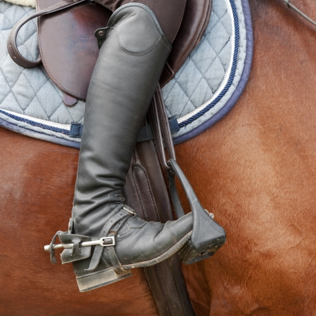 spurs: Close up of jockey riding boot, horses saddle and stirrup