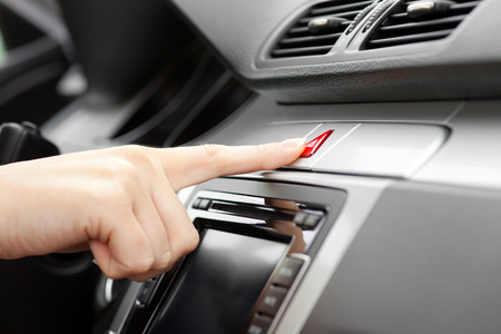 control panel lights: hand pressing Car emergency lights button on dashboard