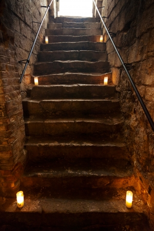 Spooky dungeon stone stairs in old castle photo