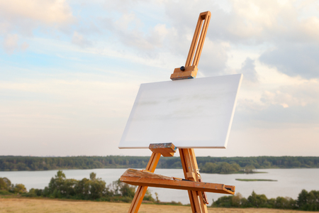 A blank canvas rests on a easel on lake landscape Stock Photo - 22447691