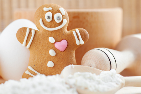 gingerbread heart: funny gingerbread man, flour, rolling pin, spoon and egg on kitchen table