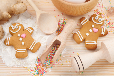 gingerbread heart: funny gingerbread men, flour, rolling pin, spoon and ginger on kitchen table Stock Photo