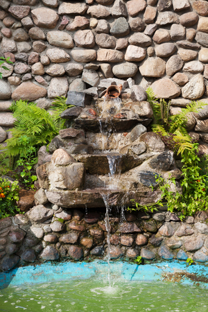 Decorative garden waterfall and pond made of stone  photo