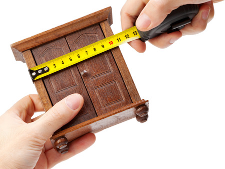 carpenter vise: woodworker measuring wardrobe with a tape measure, carpentry concept