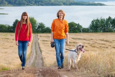 mother and her daughter with dog walking near lake photo