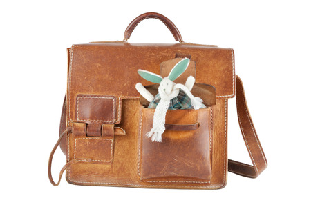 saddlebag: brown shoulder bag with cute toy rabbit in pocket, isolated Stock Photo