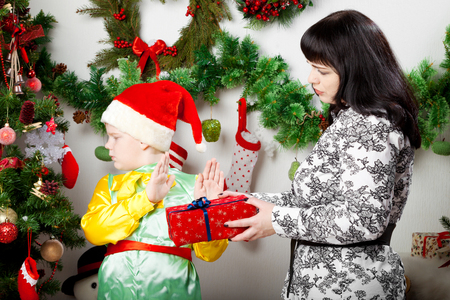 disinclination: boy refusing Christmas gift box from mother