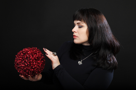 medium woman or fortune teller holds red magic ball photo