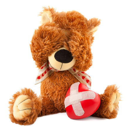 cuddly toy: sad teddy bear with broken heart on white Stock Photo