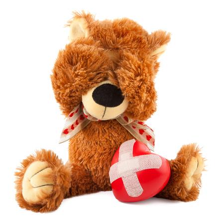traurig Teddybär mit gebrochenem Herzen auf weißem