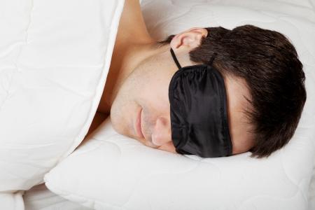 slumbering: Man with Sleeping mask sleep lying in bed Stock Photo