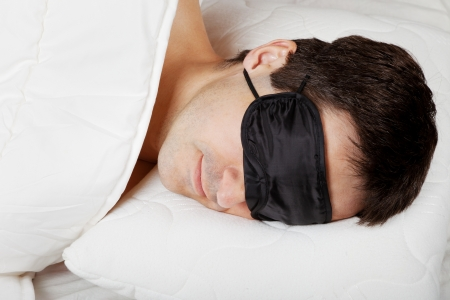 snoozing: Man with Sleeping mask sleep lying in bed Stock Photo