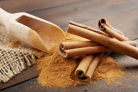 Cinnamon sticks and cinnamon powder in wooden scoop, on table Stock Photo