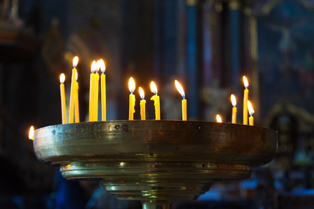 dimly: Several tall candles lit in a dark room in church