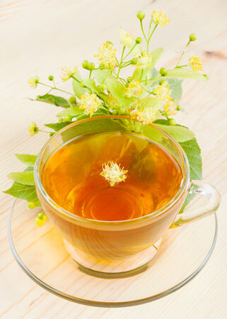 traditional healer: linden flowers and cup of healthy tea, herbal medicine
