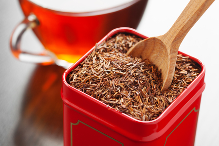 red bush tea:  rooibos in tea tin box and wooden spoon closeup