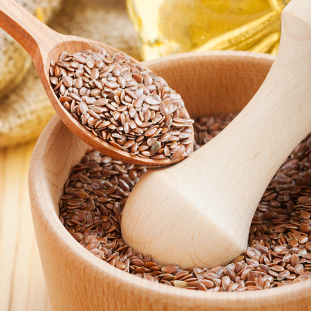 brown flax:  mortar with flax seeds, linseed in wooden spoon Stock Photo