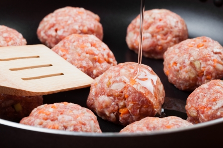 poured: meatball from minced meat in frying pan, Pouring oil and  wooden spatula