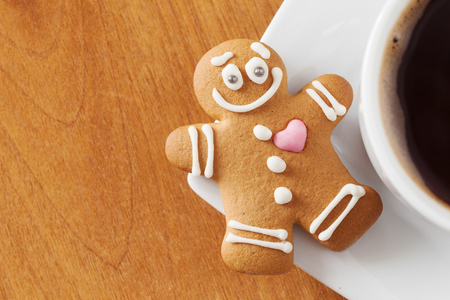 smiling gingerbread man and coffee cup on table photo
