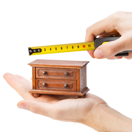 woodworker measuring chest of drawers with a tape measure, carpentry concept photo