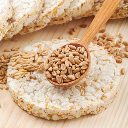 crispbread: Pane croccante cracker, cereali e cucchiaio di legno con grano Archivio Fotografico