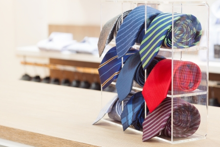 set of rolled up neck ties on plastic shelf in a shop photo