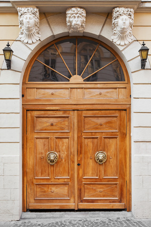 heads old building facade: vintage Entrance door decorated with Door knocker - lion head