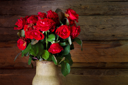 Beautiful roses with frech and wilted buds in ceramic jug on rustic wooden wand background photo