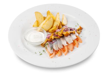 ensalada rusa: arenque filetes de pescado con patatas, setas de miel y tomate en el plato Foto de archivo