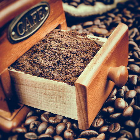 Vintage stylized photo of coffee grinder and coffee beans close up photo