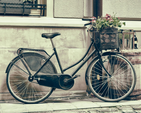 Vintage stylized photo of Old bicycle carrying flowers as decoration