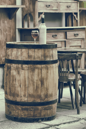 Vintage stylized photo of wooden barrel with bottles of wine and glass, chair and table in outdoor cafe Stock Photo