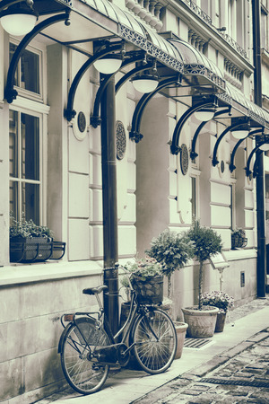 Vintage stylized photo of Old bicycle carrying flowers outdoors