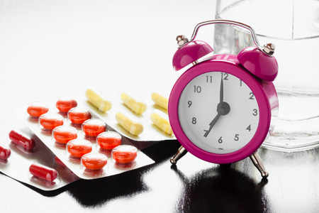 Alarm clock and medicll pills on bedside table photo