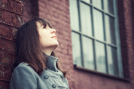 feeling up: pensive beautiful young girl standing near a brick wall and looking up Stock Photo