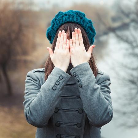ojos tristes: Muchacha bonita joven con las manos sobre los ojos al aire libre