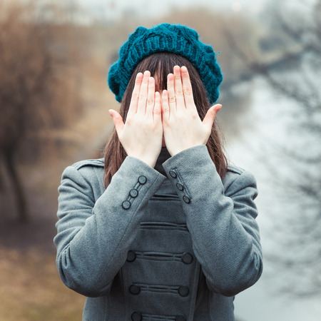 shaken: young pretty girl with hands over eyes outdoors Stock Photo