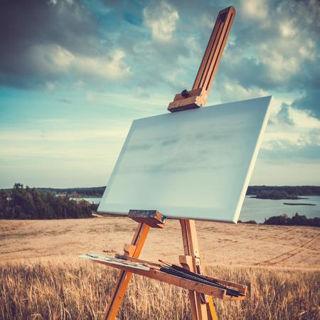 空白のキャンバスにかかっている様式化された湖の風景、レトロなイーゼル
