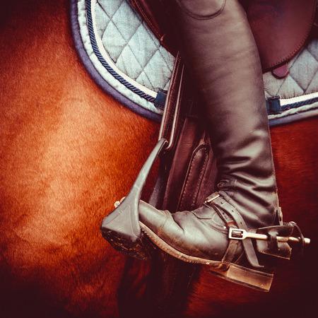 saddle: vintage stylized photo of jockey riding boot, horses saddle and stirrup