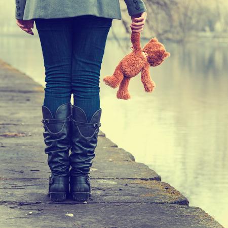 fille triste: Triste fille solitaire avec ours en peluche près de la rivière