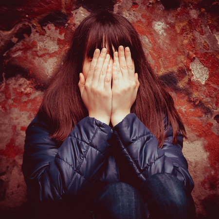 long depression: teenager girl with hands over eyes near dramatic red wall outdoors Stock Photo