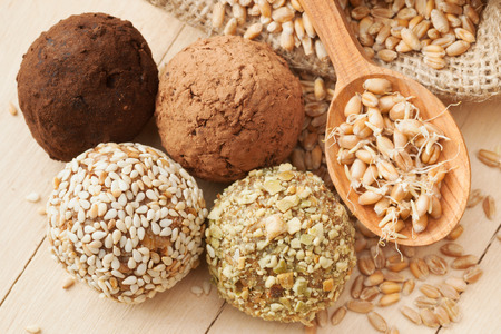 macrobiotic: macrobiotic healthy food: balls from ground wheat sprouts with sesame, pumpkin seeds, cocoa and chocolate sprinkles; sprouted grains in wooden spoon and sack on kitchen table