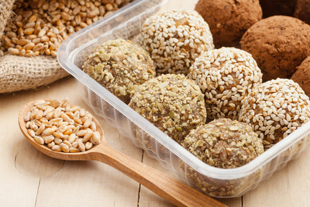 macrobiotic: macrobiotic healthy food: balls from ground wheat sprouts with sesame, pumpkin seeds and chocolate sprinkles in plastic box; sprouted grains in wooden spoon Stock Photo