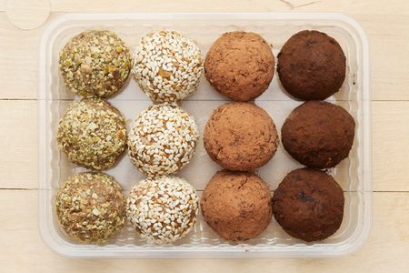 macrobiotic: macrobiotic healthy food: balls from ground wheat sprouts with sesame, pumpkin seeds and chocolate sprinkles in plastic box Stock Photo