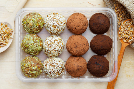 macrobiotic: macrobiotic healthy food: balls from ground wheat sprouts with sesame, pumpkin seeds and chocolate sprinkles in plastic box; sprouted grains in wooden spoon on table, top view Stock Photo