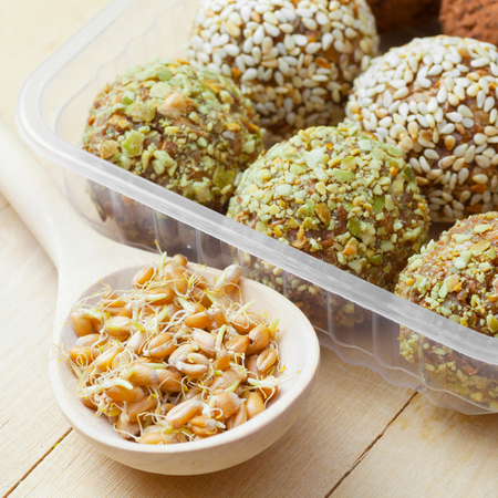 macrobiotic healthy food: balls from ground wheat sprouts with sesame and green pumpkin seeds sprinkles in plastic box; sprouted grains in wooden spoon