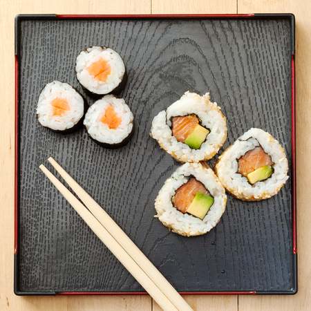 sushi rolls assortment on black plate and wooden chopsticks, top view photo