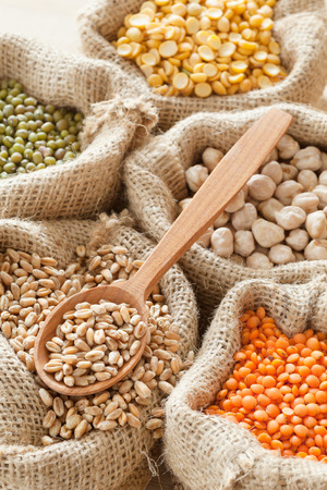 hessian bags with wheat,  peas, chick peas, red lentils and green mung, wooden spoon